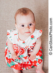baby girl in a dress with red flowers