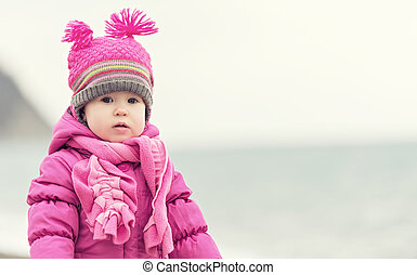 baby girl in a pink hat and scarf