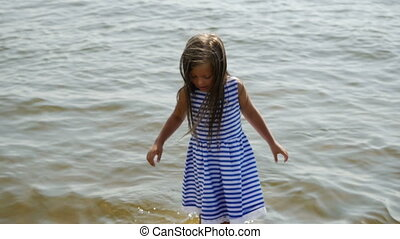 baby girl in a striped dress and runs