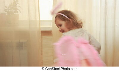 Baby girl in angel costume or fairy laughs and dances....