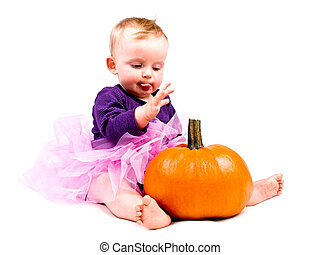 Baby girl in costume with halloween pumpkin