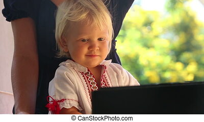baby girl in embroidery dress watching cartoon closeup