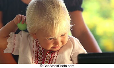 baby girl in embroidery dress watching cartoon closeup