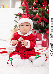Baby girl in front of christmas tree