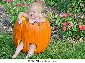 baby girl in Halloween pumpkin