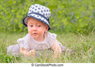 Baby girl in hat, panama. Toddler lying in the grass.