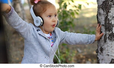 Baby girl in headphones listening to music and singing a song in a park with birches