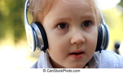 Baby girl in headphones listening to music and singing a song. portrait closeup.