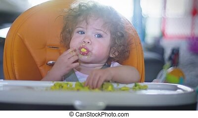 Slow motion of a baby girl sitting in her high chair feeding herself avocados...baby led weaning