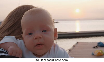 Baby girl in mothers hands outdoor at sunset