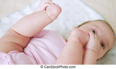 baby girl in pink clothes lying on her back on a diaper in...