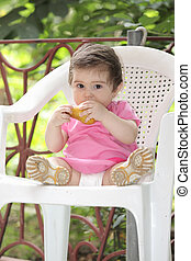 Baby girl in pink eating pear