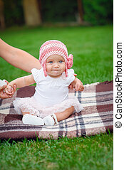 baby girl in pink knitted hat sitting on a rug in the park