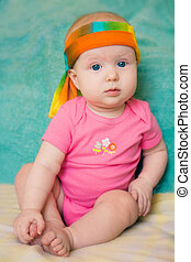Baby girl in pink t-shirt on green