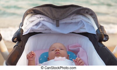 Baby girl in pram at the seaside