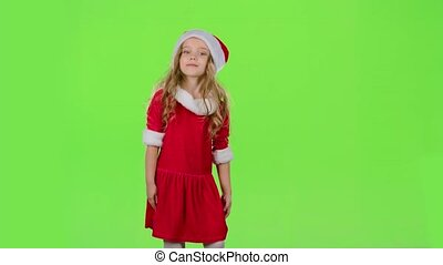 Baby girl in red New Year costume is dancing. Green screen