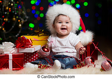 baby girl in Santa Claus hat with gifts under Christmas tree