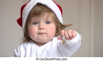 Baby girl in Santa Claus red hat at home