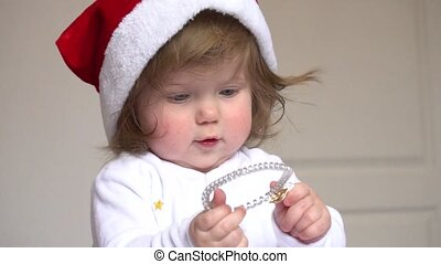 Baby girl in Santa Claus red hat playing