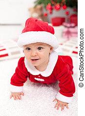 Baby girl in santa outfit crawling