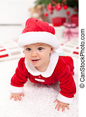 Baby girl in santa outfit crawling