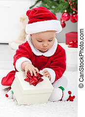 Baby girl in santa outfit opening a present sitting on the...