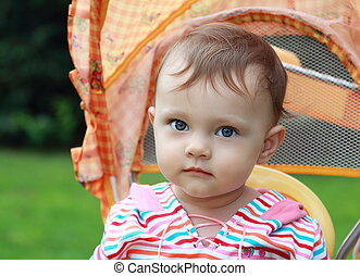 Baby girl in stroller looking outdoors summer green background. Closeup portrait