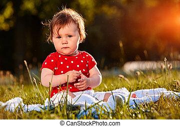 Baby Girl In Summer Dress Sitting In Field