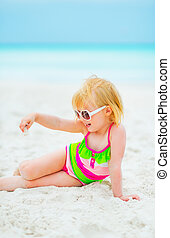 Baby girl in sunglasses playing with sand on beach