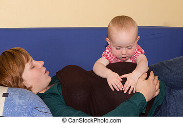 Baby girl investing her pregnant mothers belly
