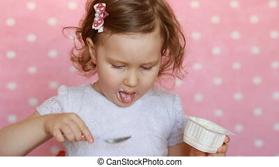 Baby girl is eating a yogurt for breakfast. The child eats...