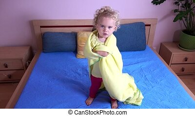 Baby girl jump on bed wrapped in plaid.