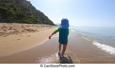 Baby girl kid running on the beach, honest happiness concept in summer vacation