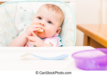 Baby girl - Little girl eating baby food in high chair.