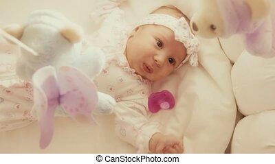 Baby girl looking at defocused toy mobile in her cot -...