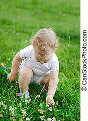 Baby girl looking for flowers in grass
