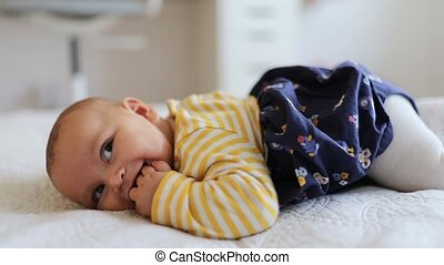 FHD video of a baby girl lying down on a bed and wearing a white and yellow striped shirt and a blue skirt