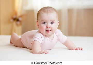 baby girl lying on white bed