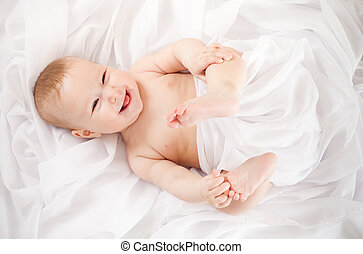 baby girl lying on white fabric and holding legs