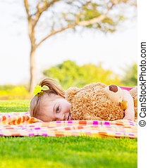 Baby girl lying with soft toy