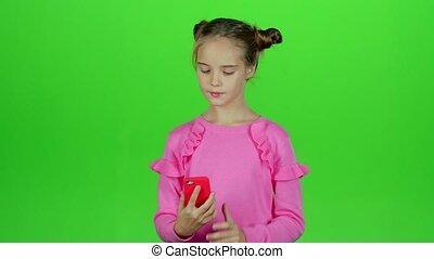 Baby girl makes selfie on her phone. Green screen. Slow motion