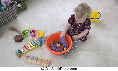 Baby girl mix wooden bricks in bowl with big spoon. Cooking...