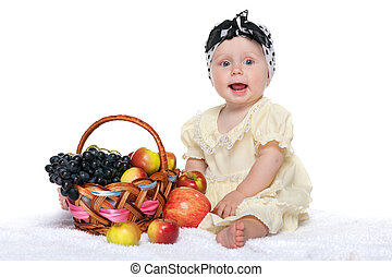 Baby girl near a basket with vegetables