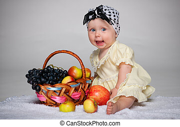 Baby girl near the basket with vegetables
