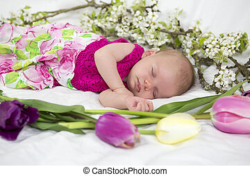 Baby girl of one month in pink with spring flowers.