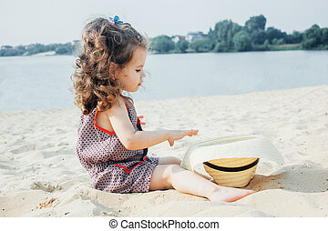 Baby girl on a beach with the straw hat