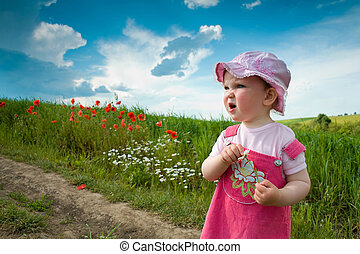 Baby-girl on a lane amongst a field