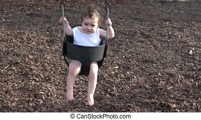 baby girl on a swing at the playground