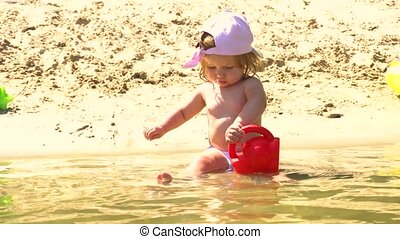 Baby girl on beach playing with watering pot - Baby girl in...