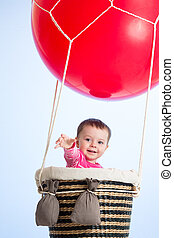 baby girl on hot air balloon in the sky